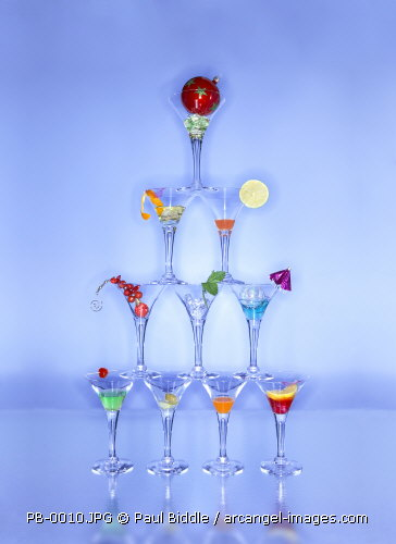 christmas cocktail glasses in a pyramid shape, with the remains of drinks & decorations in them